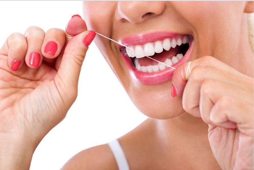 Woman Cleaning dental bridge